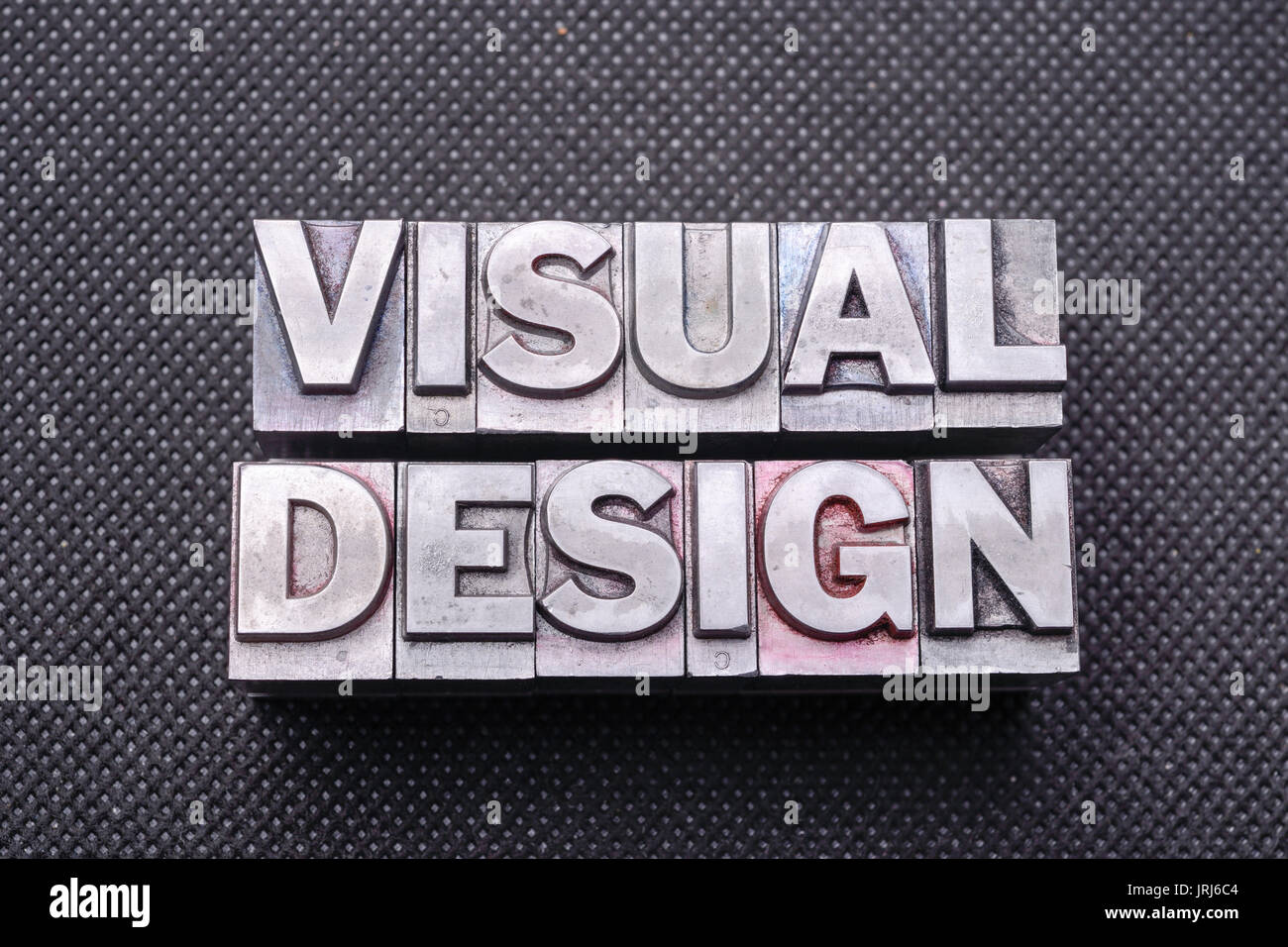visual design phrase made from metallic letterpress blocks on black perforated surface - Stock Image