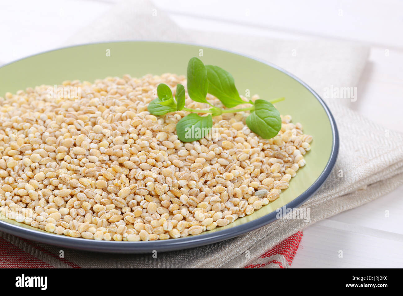 plate of pearl barley on folded place mat - close up - Stock Image