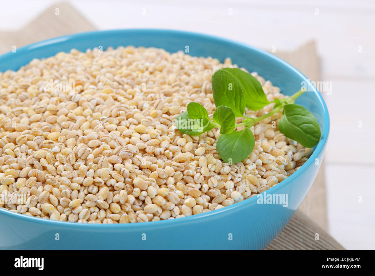 bowl of pearl barley on beige place mat - close up - Stock Image