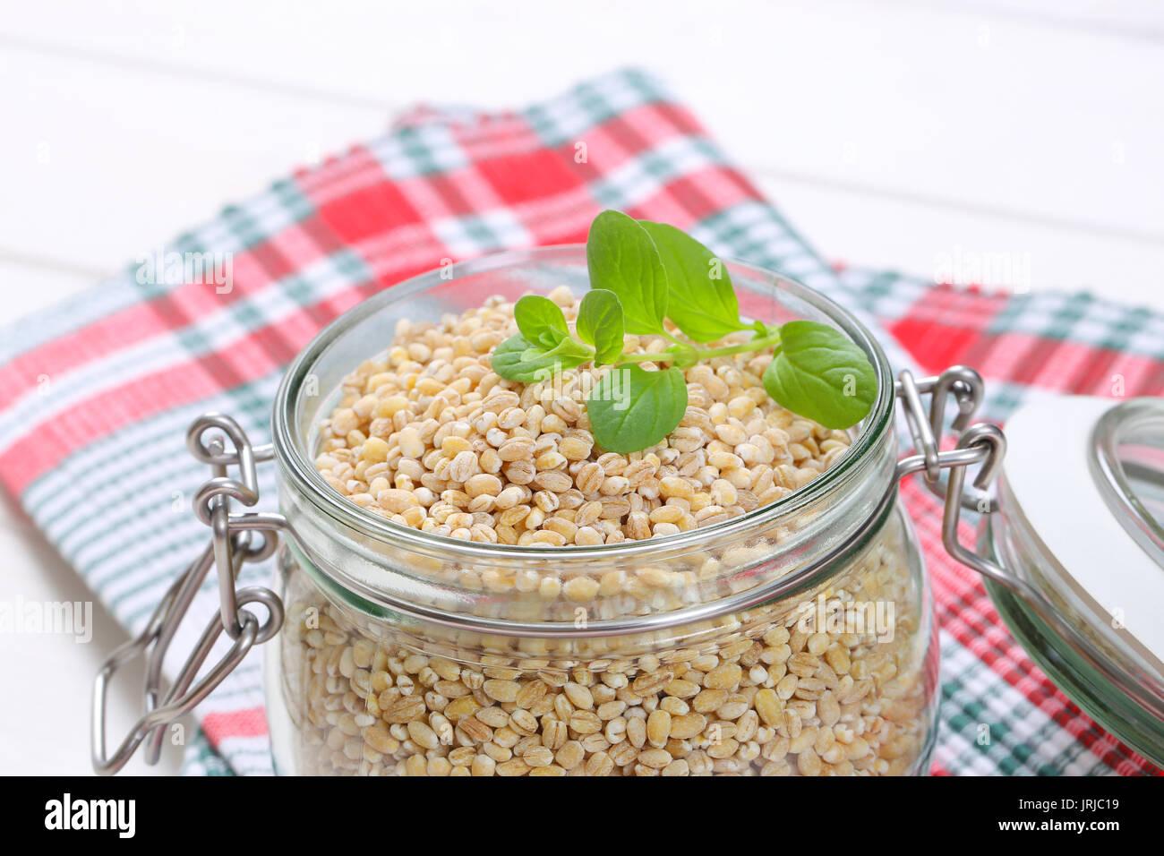 jar of pearl barley on checkered place mat - close up - Stock Image