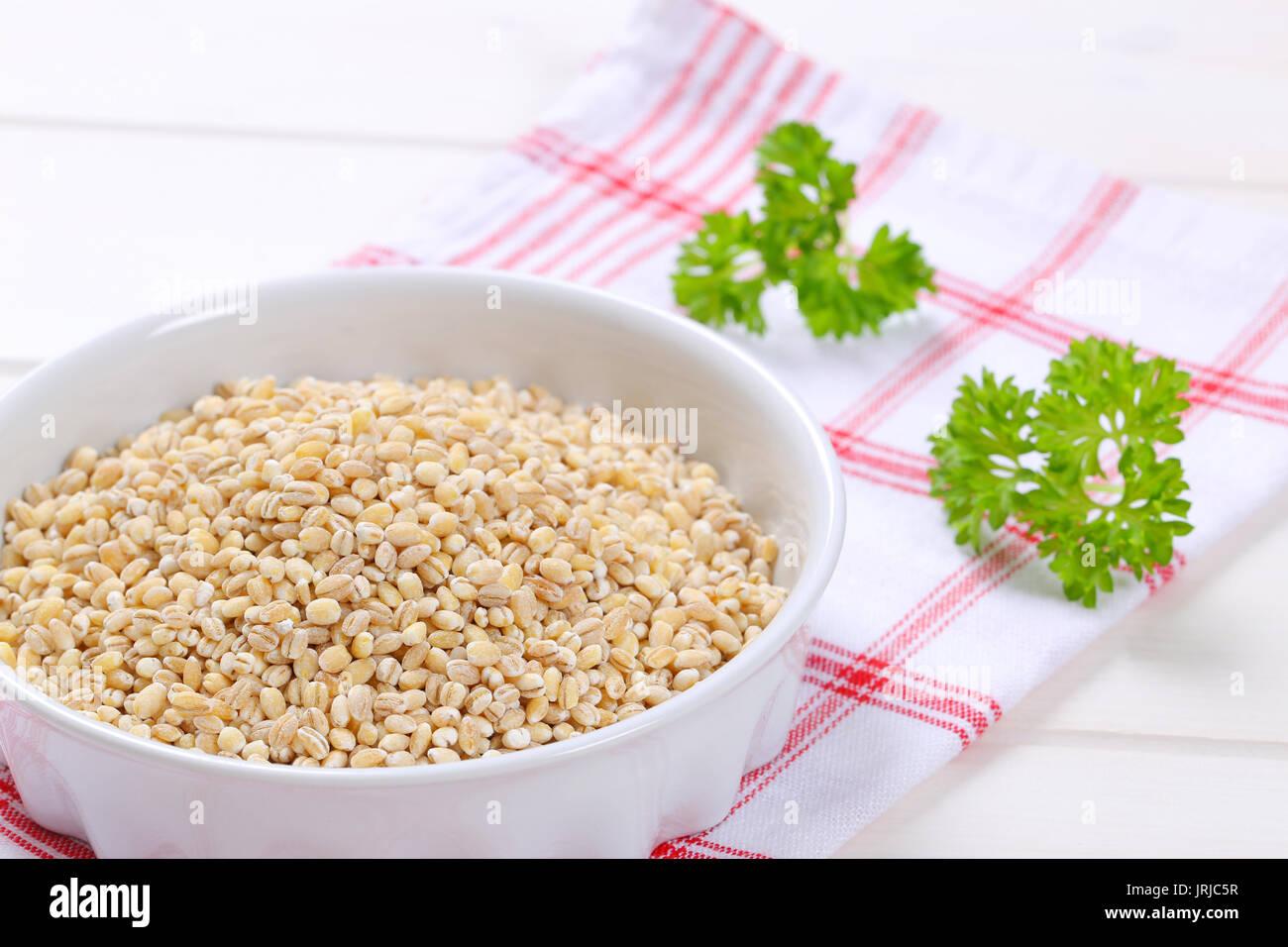 bowl of pearl barley on checkered dishtowel - close up - Stock Image