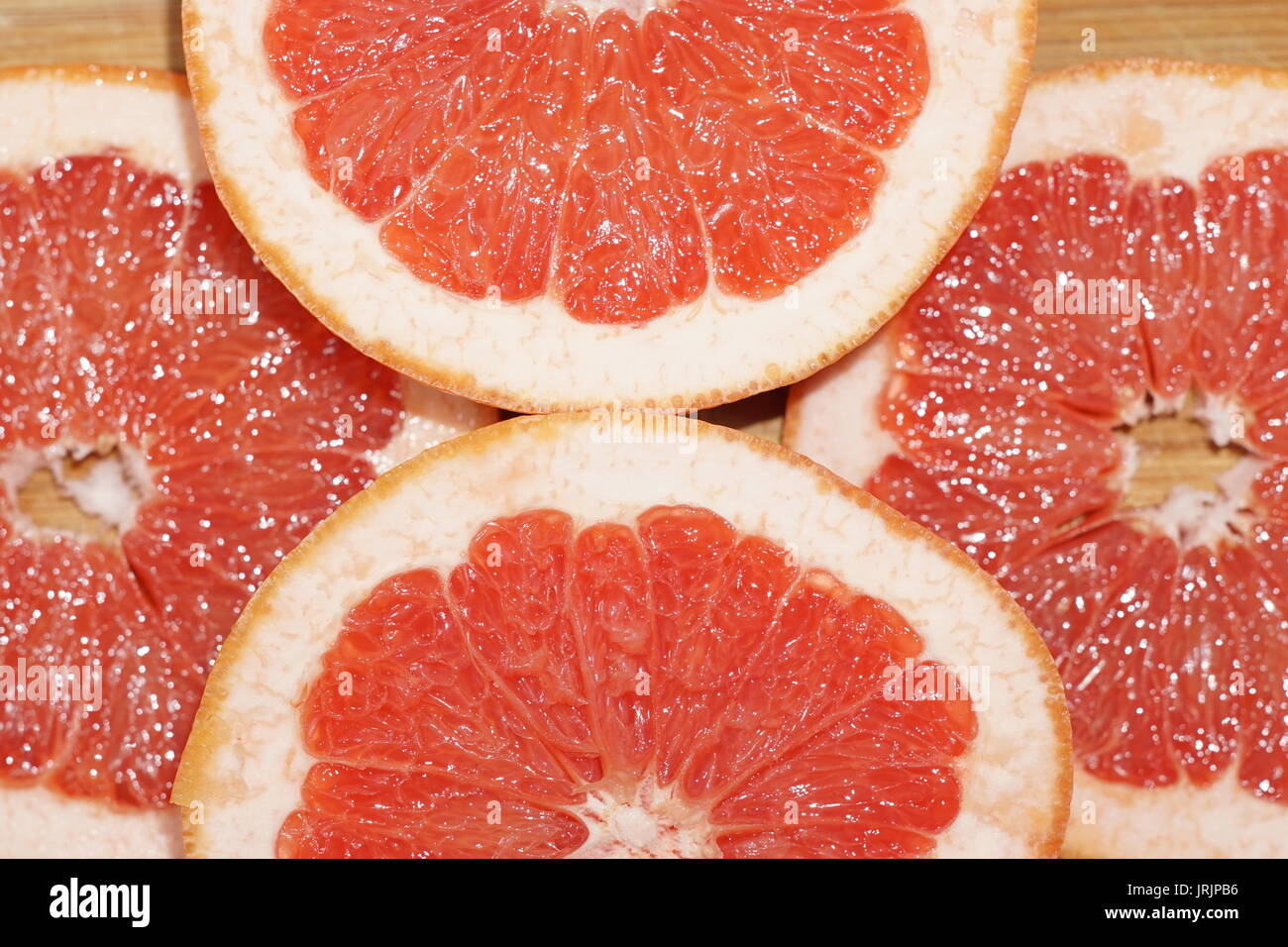 Grapefruit cut on slices and arranged on wooden plate shining from reflected light - Stock Image