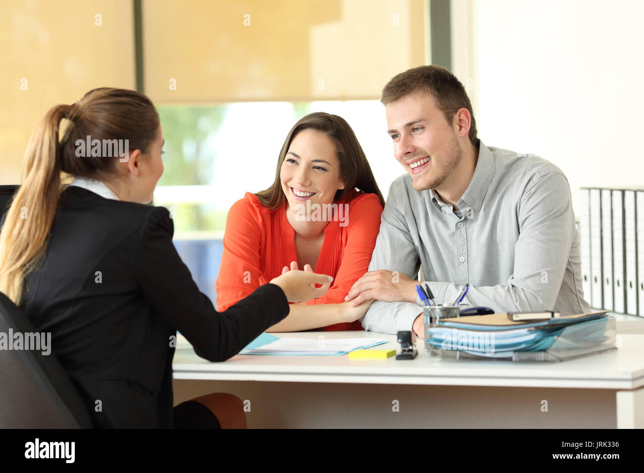 Happy couple being attended by office worker at office - Stock Image