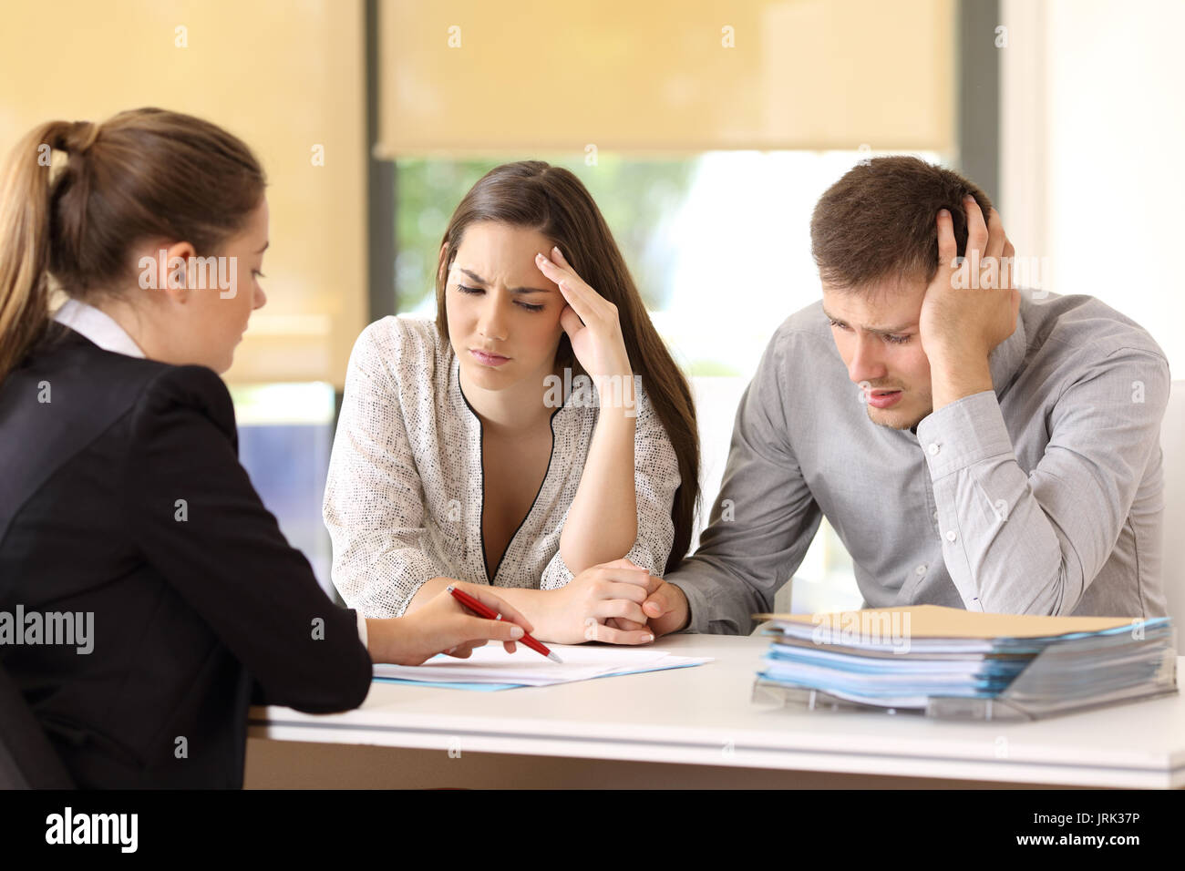 Saleswoman explaining conditions of a document with bad news to a couple of worried customers at office - Stock Image
