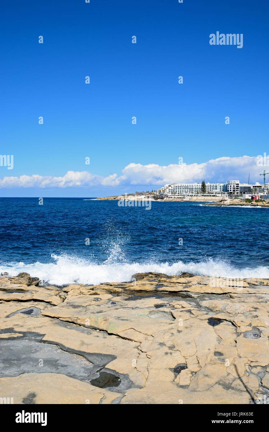 Sea crashing onto the rocky coastline with hotels and apartments to the rear, Bugibba, Malta, Europe. - Stock Image