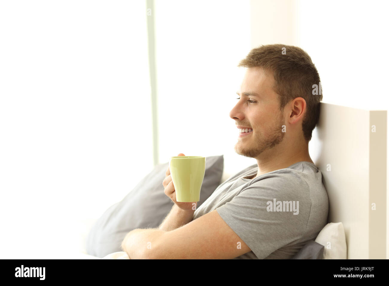 Side view of a happy man holding coffee cup having breakfast and thinking on the bed of an apartment - Stock Image
