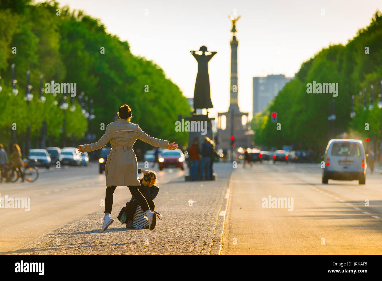 Berlin tourists, a young woman tourist leaps into the air whilst being photographed in the Strasse Des 17 Juni, center of Berlin, Germany. - Stock Image