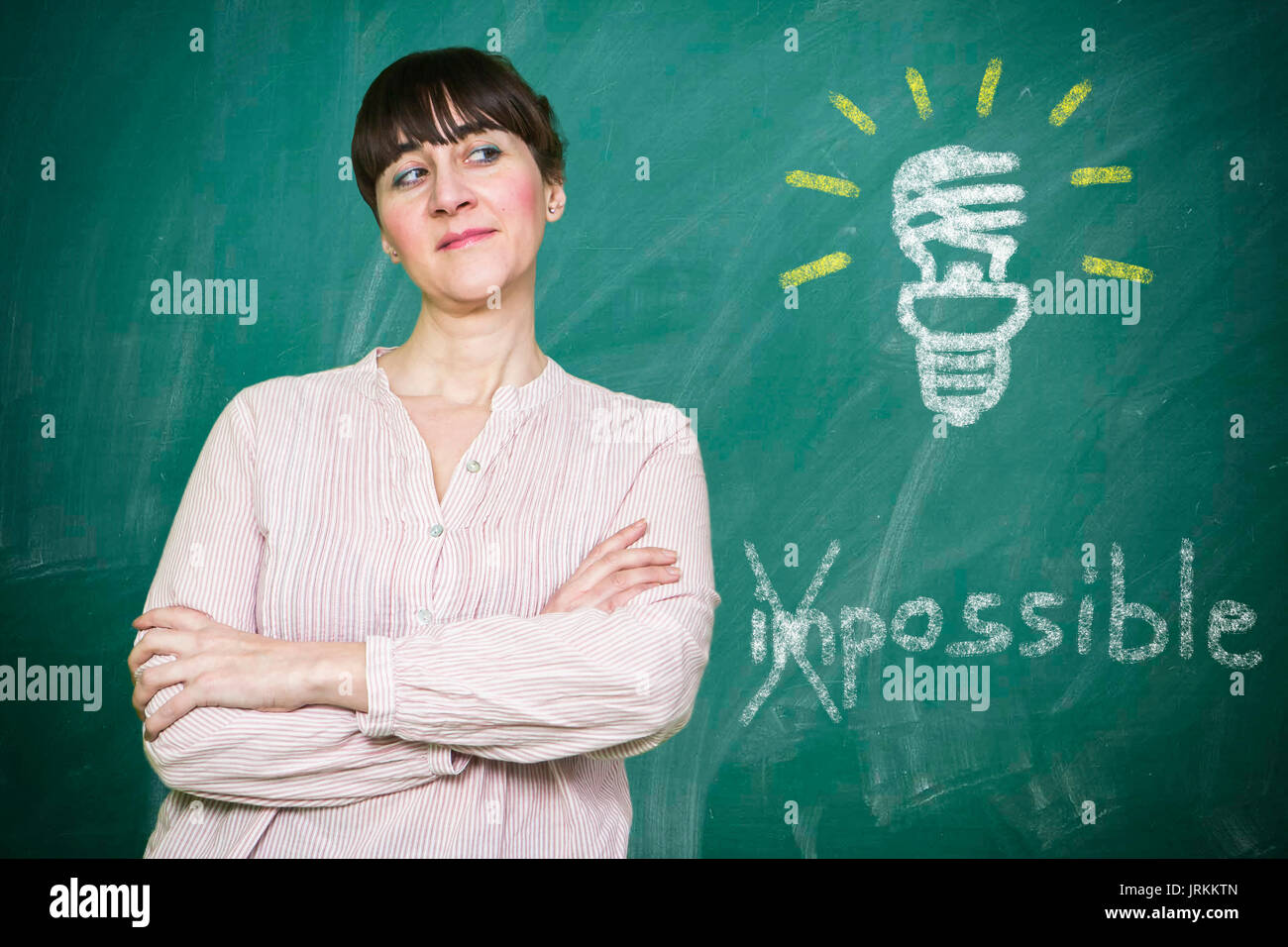 Woman smiles writes on a blackboard the concept of saving energy is possible Stock Photo