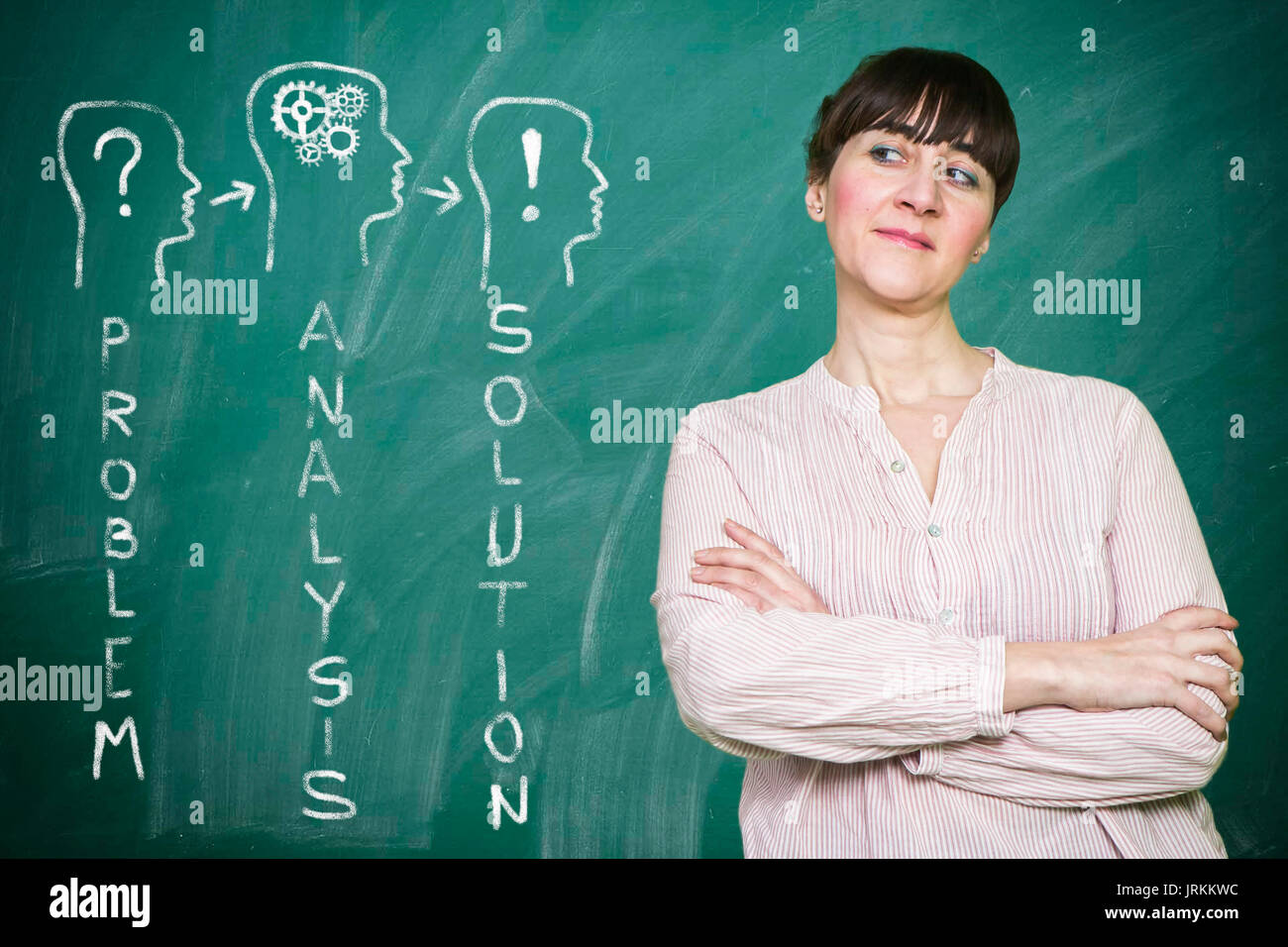 Woman smiles writes on a blackboard the concept of strategy Stock Photo