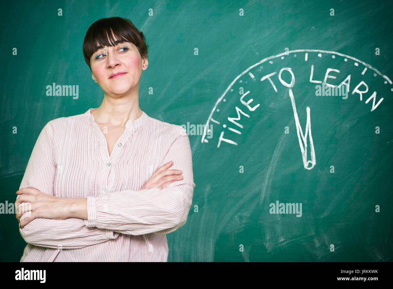 Woman smiles writes on a blackboard to learn concept Stock Photo