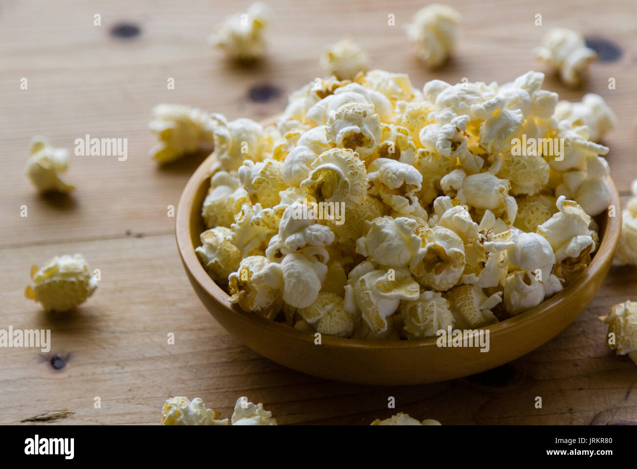 fresh salted popcorn in bowl on wooden table - Stock Image