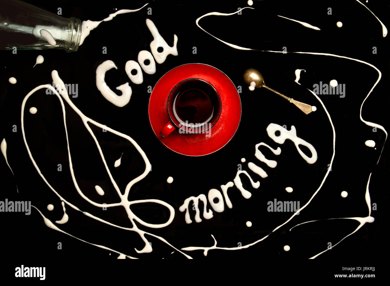 Red cup of coffee on a black background and 'Good morning!' written with milk - Stock Image