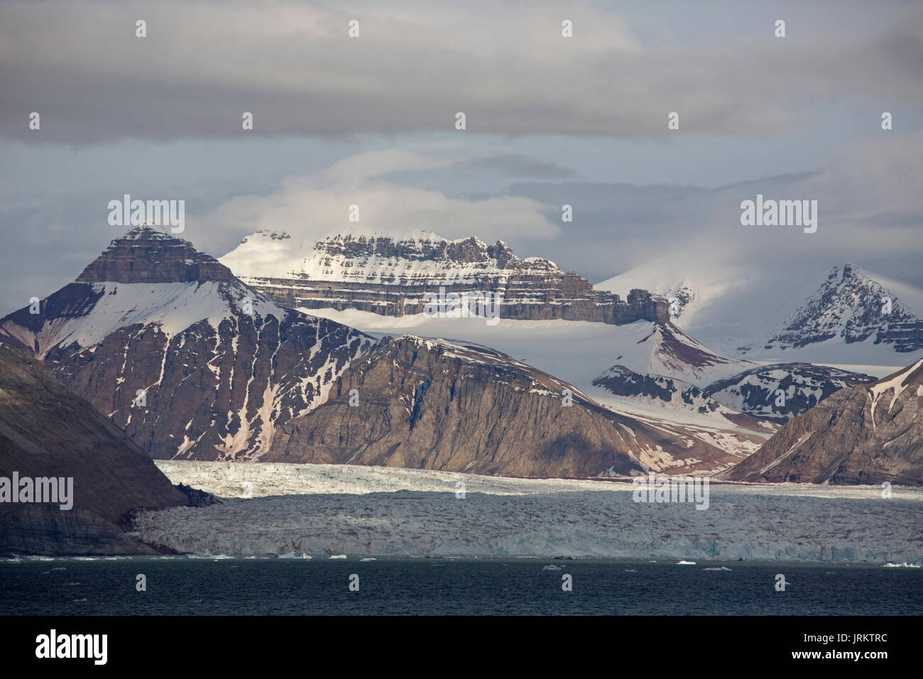 Kronebreen or Crown glacier, Kongsfjord and snow covered, pyramidal shaped mountains. Taken in June, Spitsbergen, Svalbard, Norway - Stock Image