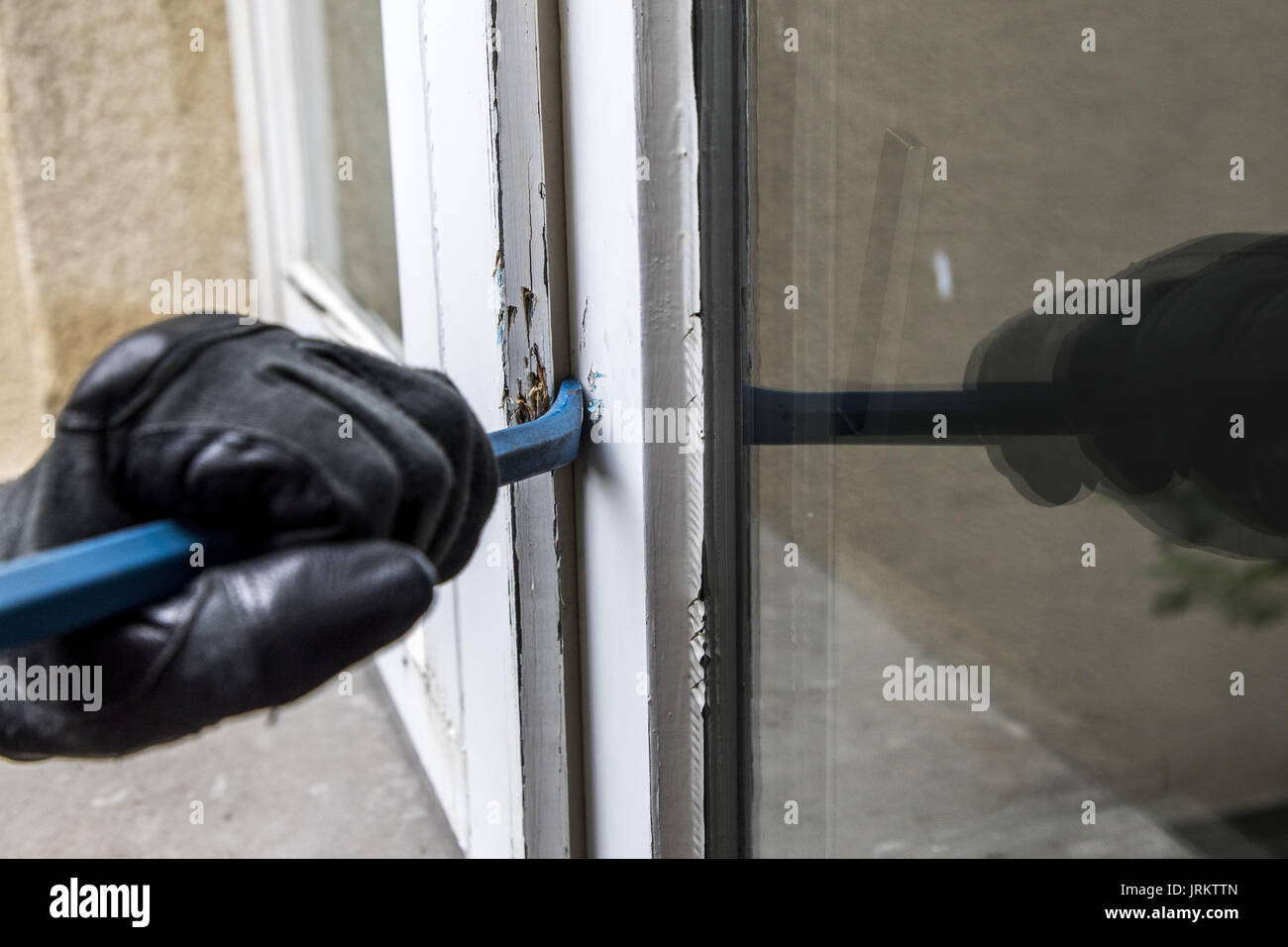 Symbol image, Apartment burglary,  burglar tries to break into an apartment, breaking up a window with tool, - Stock Image