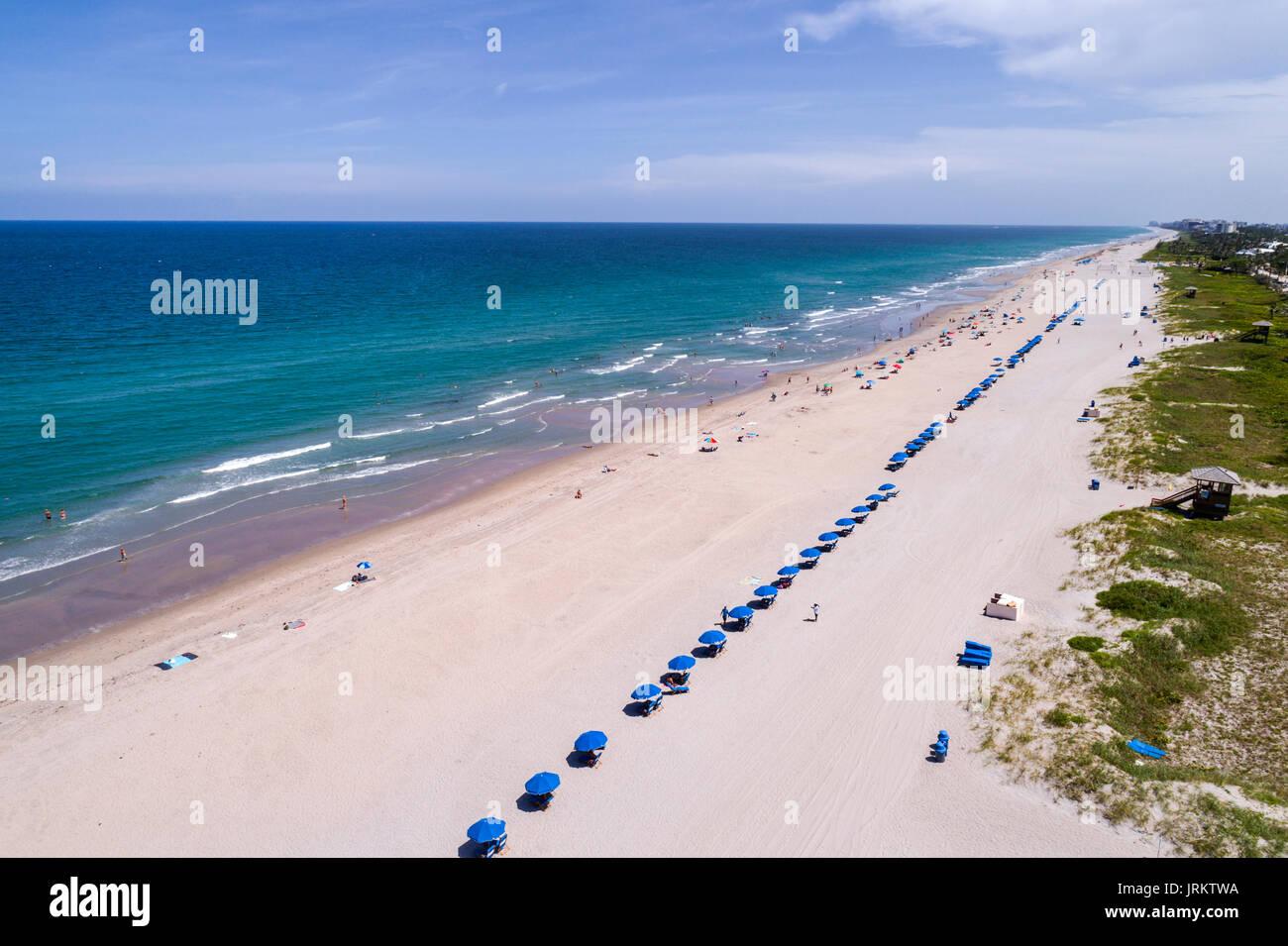 Florida Delray Beach Atlantic Ocean sand blue umbrellas aerial overhead view bird's eye above sunbathers - Stock Image