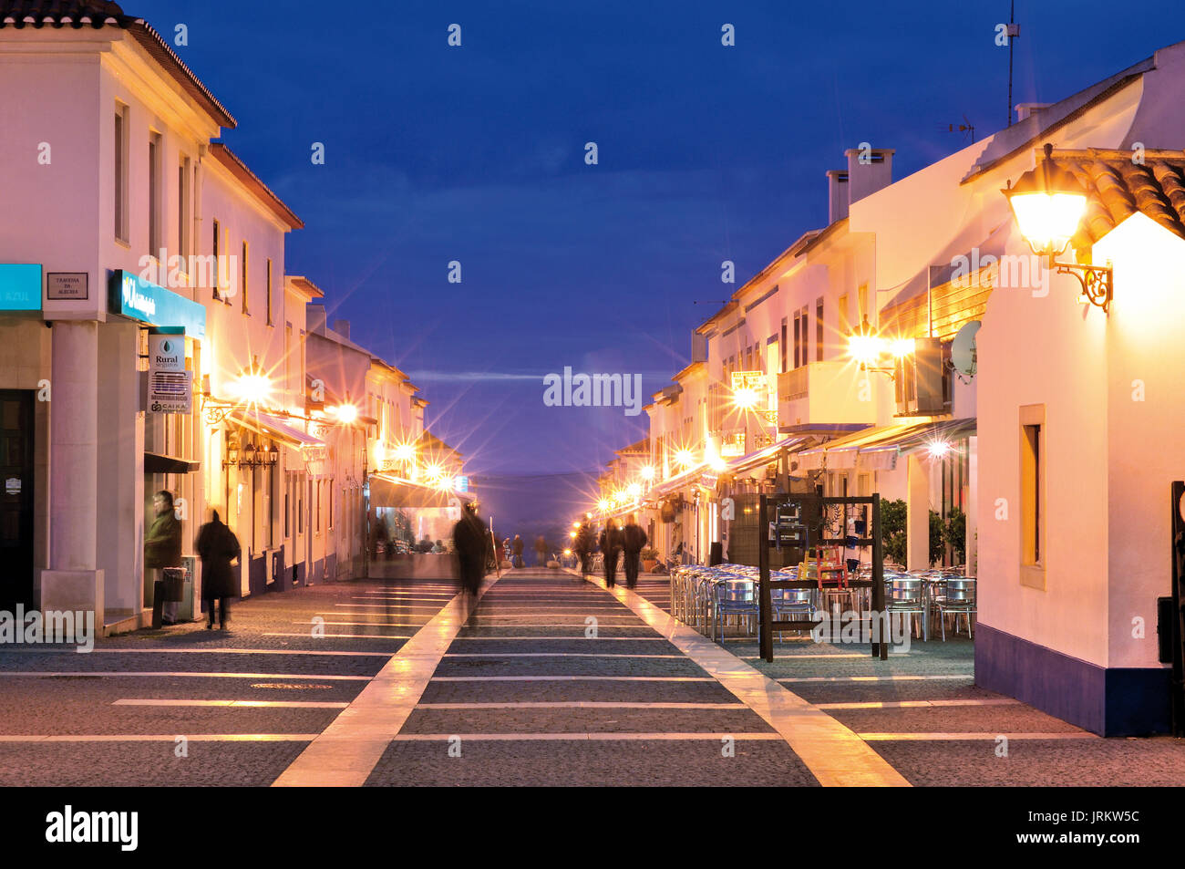 People walking along noctural illuminated main street in charming coastal village Porto Covo - Stock Image