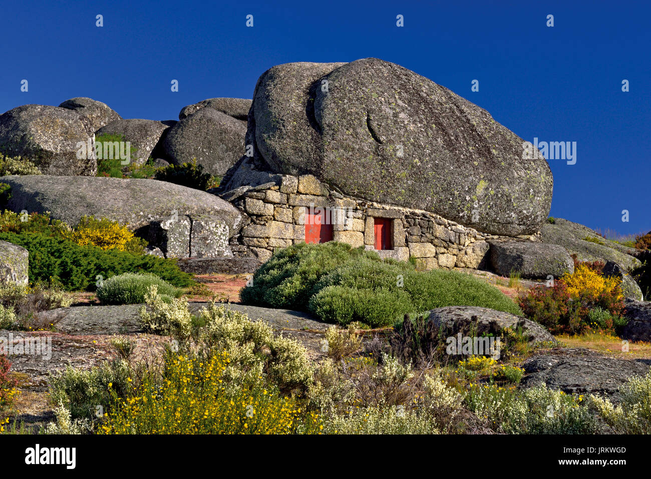 Tiny stone house under huge granite rock - Stock Image