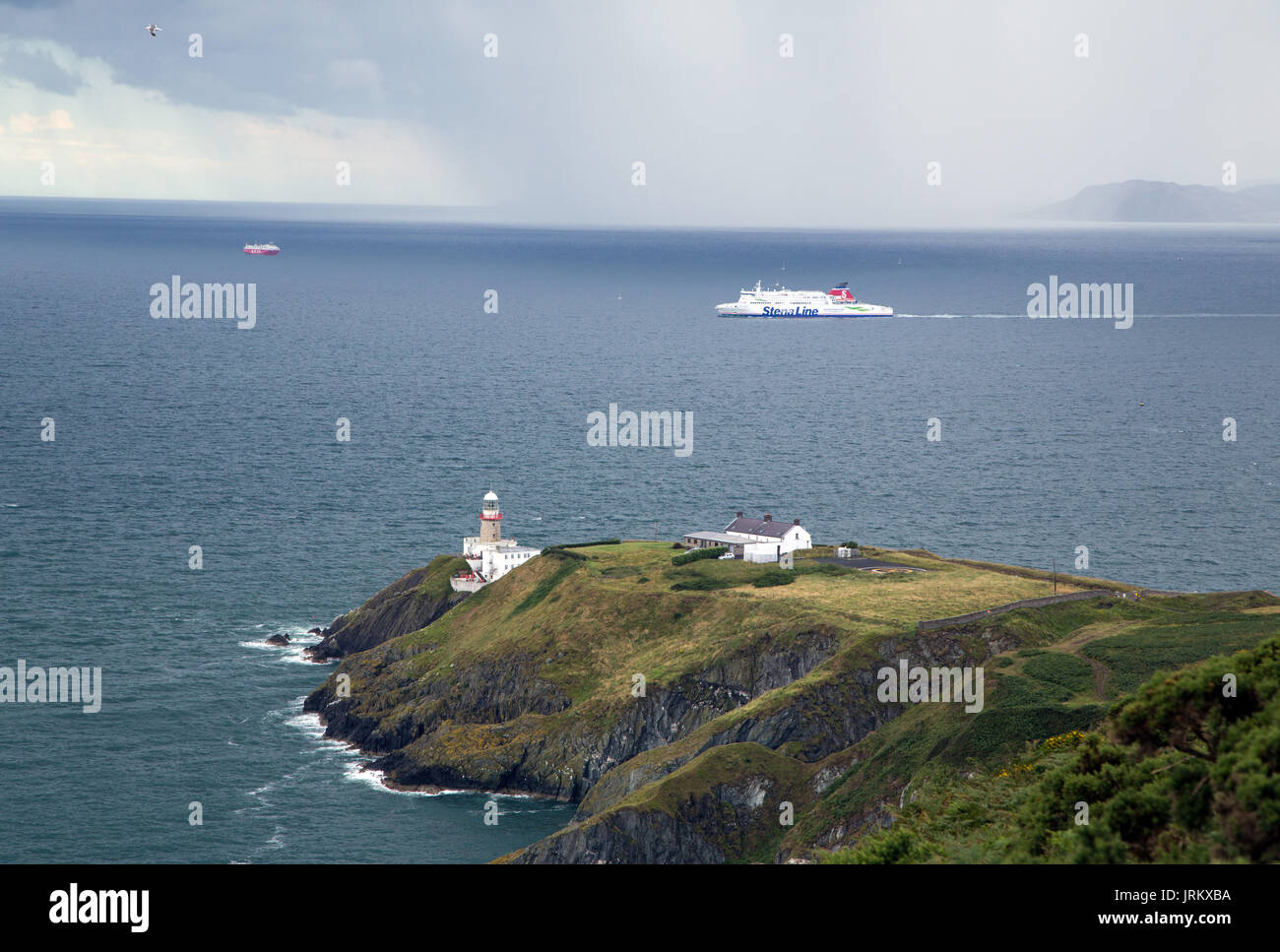 The Dún Laoghaire ferry passing Baily's Lighthouse with a rain squall in the background - Stock Image