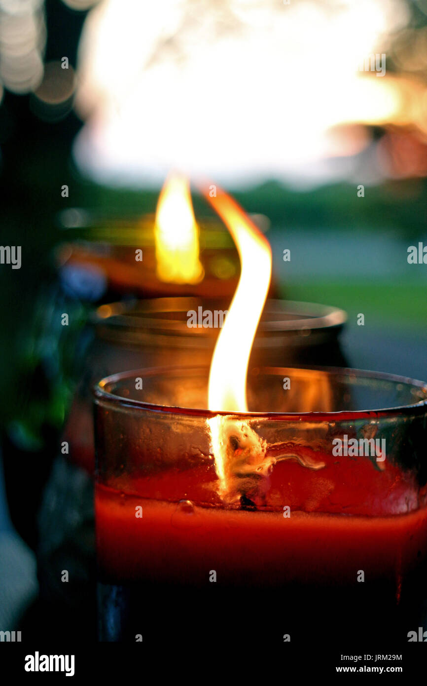 Three candles in glass jars in a row, with flames, soft focus depth Stock Photo