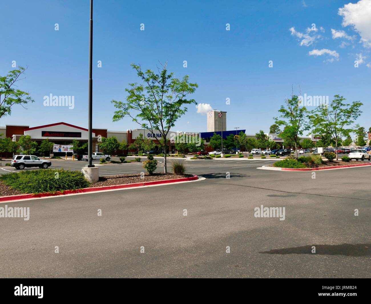 Mostly empty parking lot, strip mall, with Nestle Purina plant stack seen in the distance. Flagstaff, Arizona, USA. - Stock Image