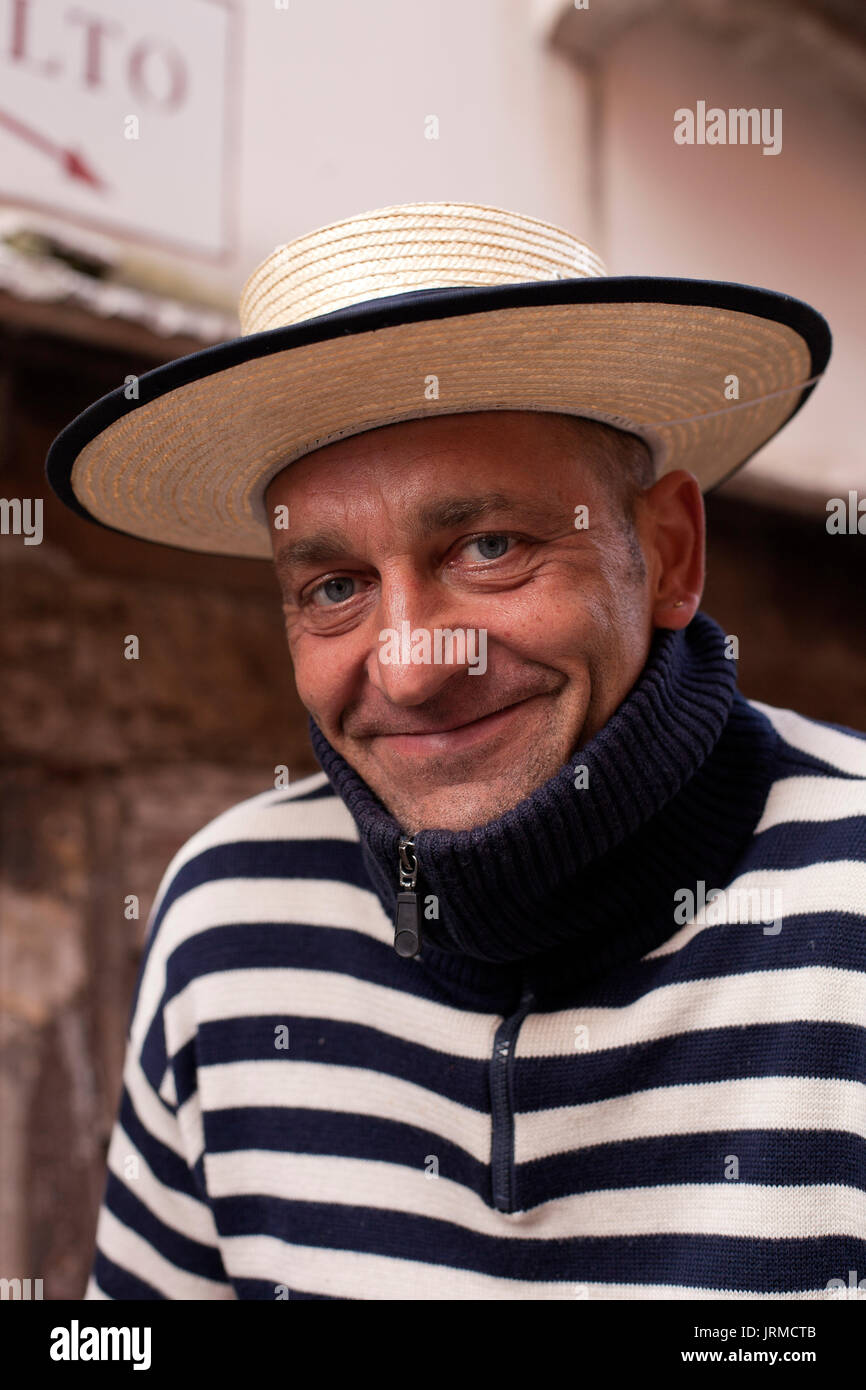 A smiling gondolier  relaxes on a bridge near The Rialto in Venice, Italy - Stock Image