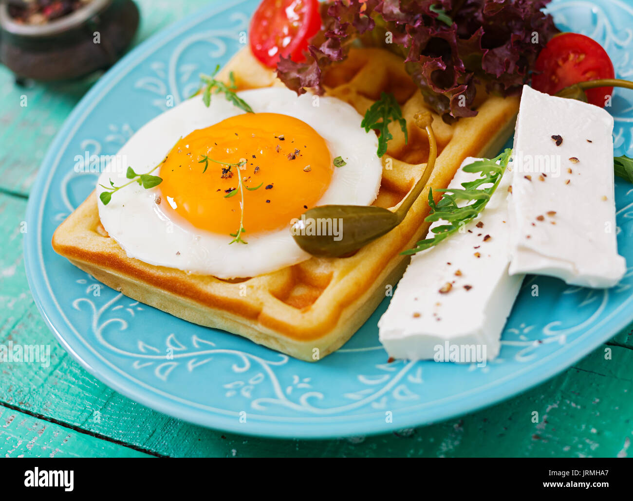 Healthy breakfast - waffles, eggs, feta cheese, tomatoes and lettuce - Stock Image