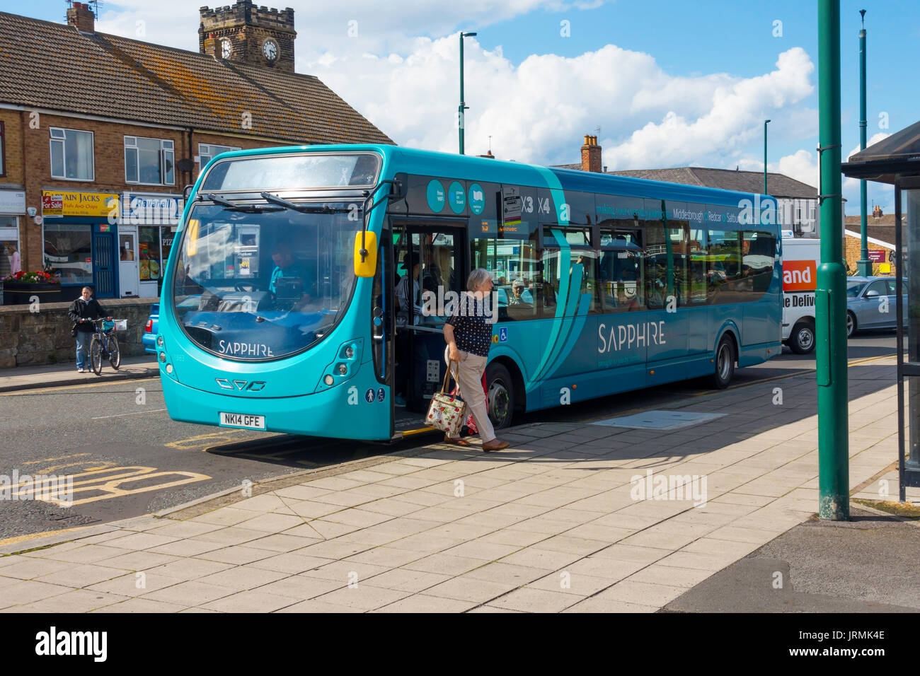 A lady alighting from an Arriva Sapphire bus providing a 15 minute interval service on selected routes countrywide here in Marske by the sea Yorkshire - Stock Image