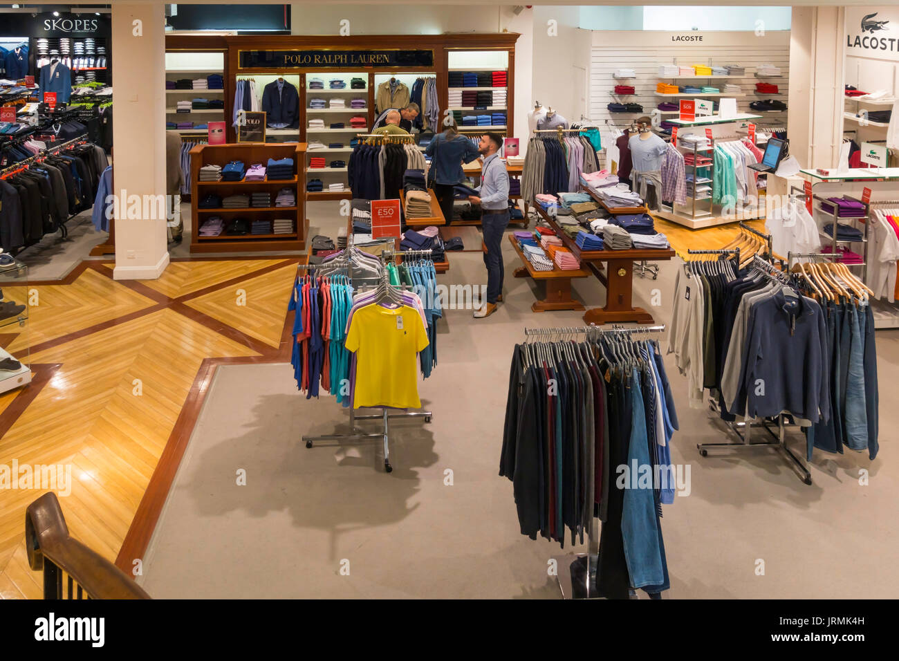 Department store mens fashion clothing department with customers buying summer sale clothing - Stock Image