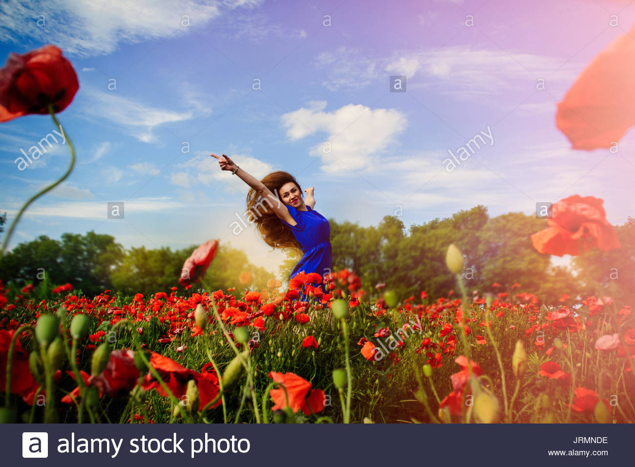Girl jumping out of flowers Stock Photo