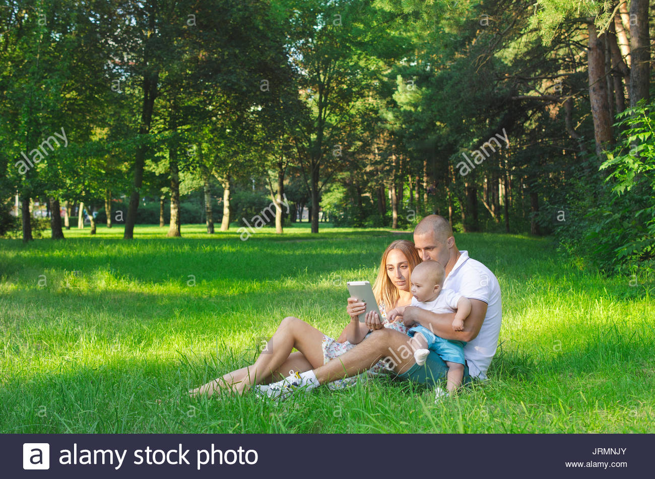 Family spending time with a tablet on nature in summer Stock Photo