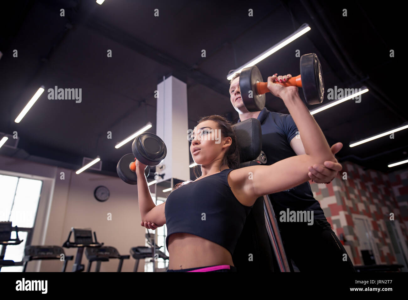 gym woman personal trainer man with weight training equipment - Stock Image