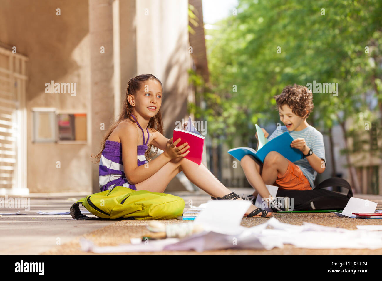 Happy boy and girl with textbooks near the school reading talking smiling Stock Photo