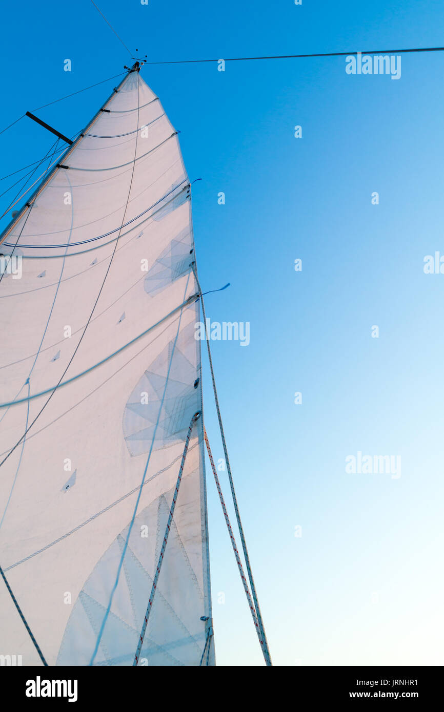 Part of hoisted mainsail of sailing boat with leech, rigging and reefing lines against blue sky - Stock Image