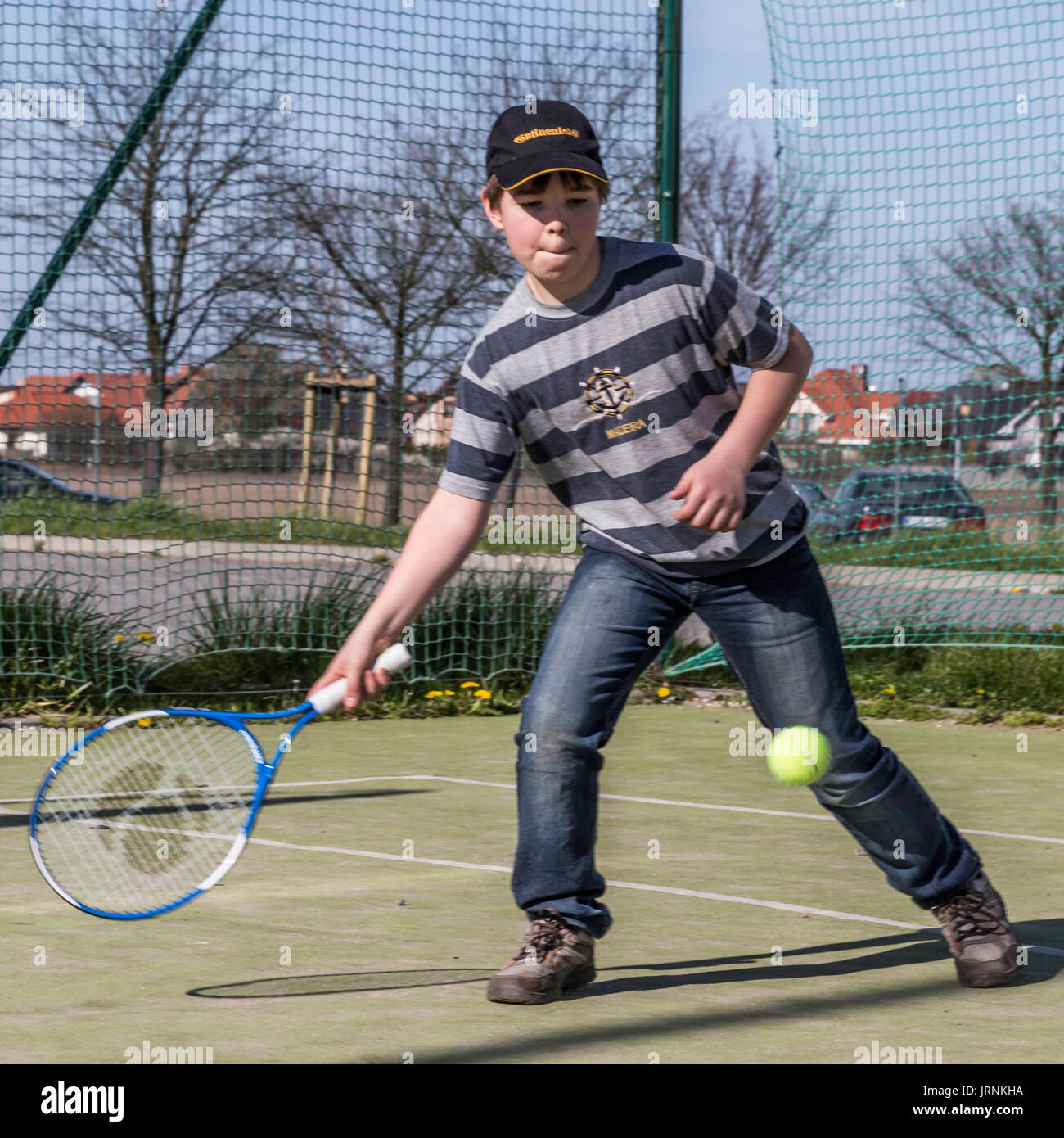 A boy or teenager playing tennis, excercise during holidays, vacation time, late summer in Poland. - Stock Image