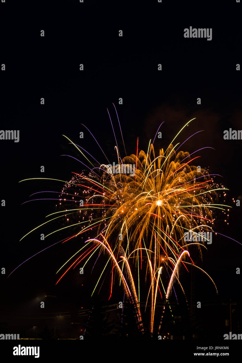 Bright fireworks display of varied colors during an evening of celebration during a national holiday. - Stock Image