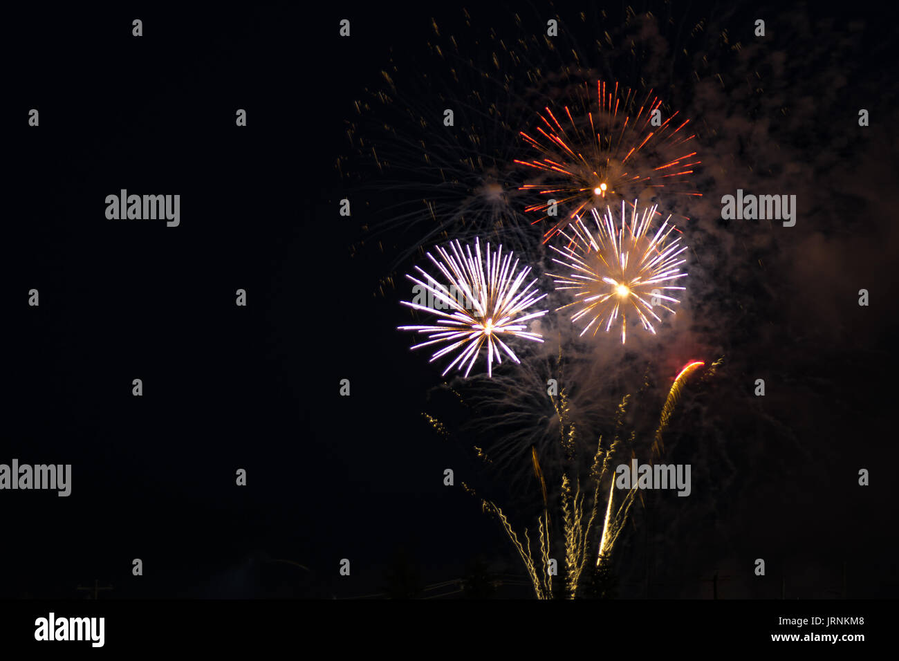 Brilliant fireworks display of red, yellow and white colors, set against a black sky during an evening of celebrating a national holiday. - Stock Image