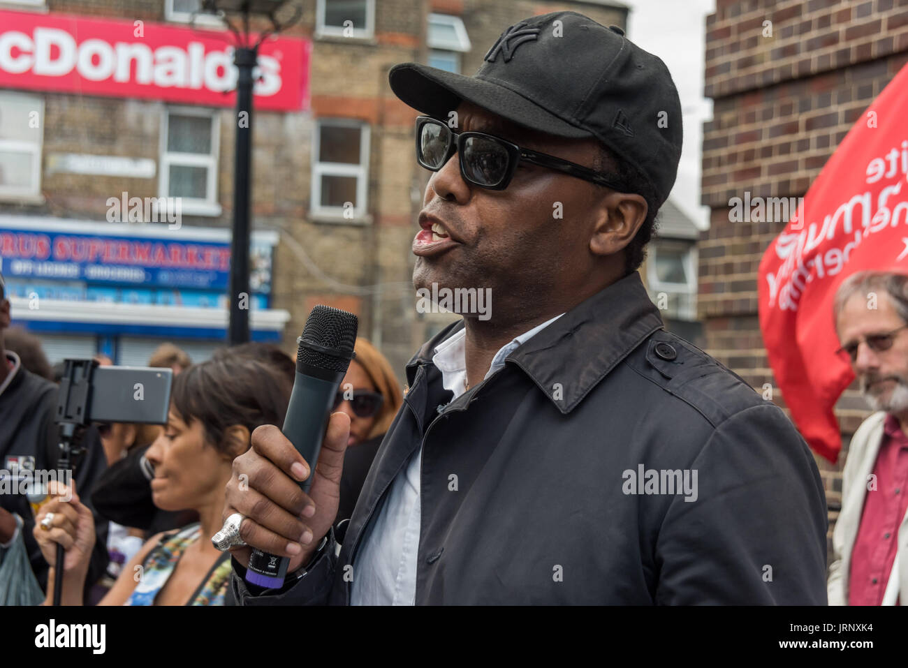 London, UK. 4th Aug, 2017. London, UK. 4th August 2017. An speaker from the Justice for Grenfell campaign gives a powerful address at the rally at Tottenham Police Station remembering the death of Mark Duggan on the sixth anniversary of his killing by police, and also the police killing of other members of the Tottenham community - Cynthia Jarrett, Joy Gardner, Roger Sylvester, Mark Duggan and Jermaine Baker and the recent murders of Rashan Charles, Darren Cumberbatch and Edson Da Costa. Led by Stafford Scott, there was poetry, a minute of silence and speeches from family members as well as - Stock Image