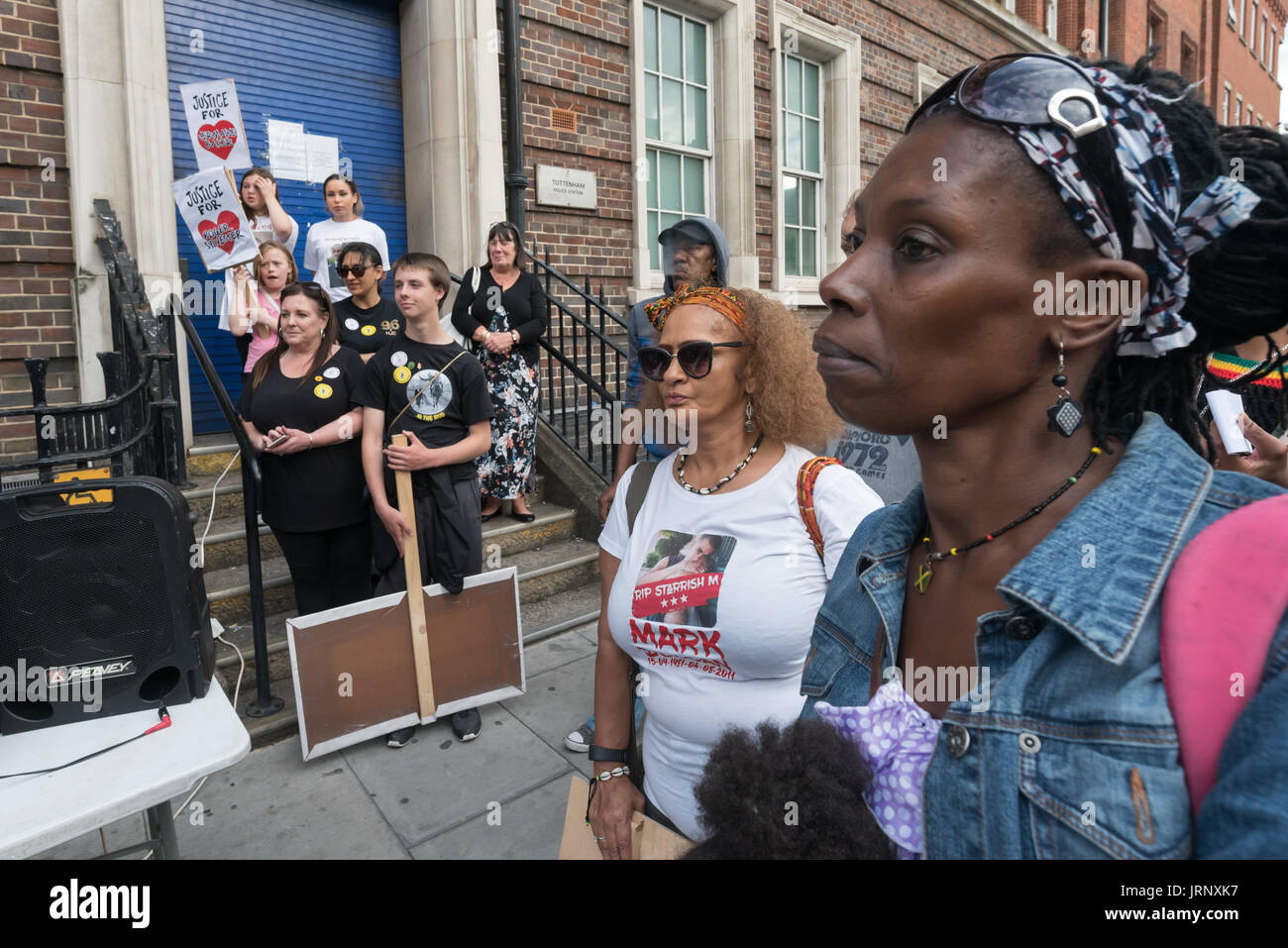 London, UK. 4th Aug, 2017. London, UK. 4th August 2017. People at the rally at Tottenham Police Station remembering the death of Mark Duggan on the sixth anniversary of his killing by police listen to Tottenham poet, Jason Nwansi. THe vent also remembered the police killing of other members of the Tottenham community - Cynthia Jarrett, Joy Gardner, Roger Sylvester, Mark Duggan and Jermaine Baker and the recent murders of Rashan Charles, Darren Cumberbatch and Edson Da Costa. Led by Stafford Scott, there was poetry, a minute of silence and speeches from family members as well as local activi - Stock Image