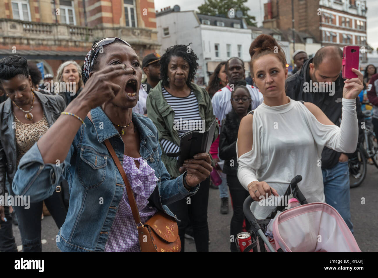 London, UK. 4th Aug, 2017. London, UK. 4th August 2017. People in the crowd react to the speaker from the Justice for Grenfell campaign, echoing his call for action from the community at the rally at Tottenham Police Station remembering the death of Mark Duggan on the sixth anniversary of his killing by police, and also the police killing of other members of the Tottenham community - Cynthia Jarrett, Joy Gardner, Roger Sylvester, Mark Duggan and Jermaine Baker and the recent murders of Rashan Charles, Darren Cumberbatch and Edson Da Costa. Led by Stafford Scott, there was poetry, a minute o - Stock Image