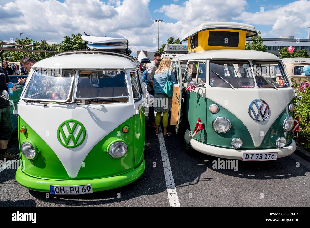Stocken, Germany. 06th Aug, 2017. Visitors watch old VW Kombis in the grounds of the Volkswagen Commercial Vehicles Plant during the Kombi Meet on the occasion of the 70th anniversary of the Volkswagen Transporter in Stocken, Germany, 06 August 2017. Photo: Peter Steffen/dpa/Alamy Live News - Stock Image