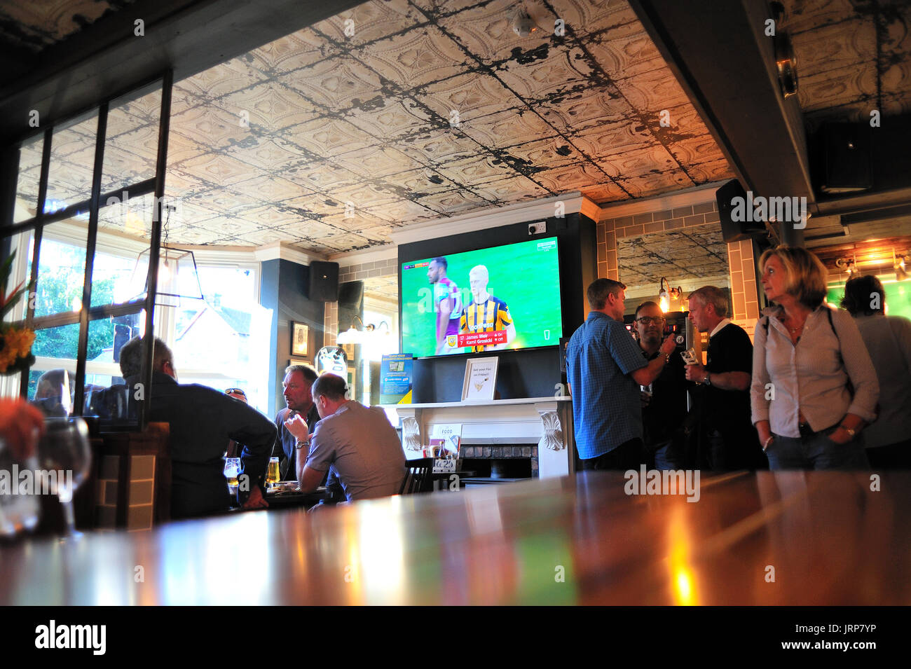 Customers in Porter Brook Pub Sheffield watching football on TV - Stock Image