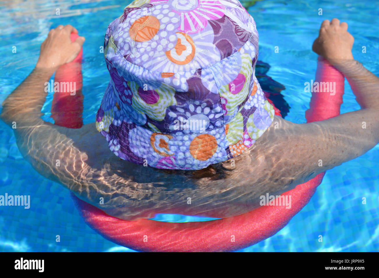 Summer vibes! Woman floating in a swimming pool using a pool noodle. - Stock Image