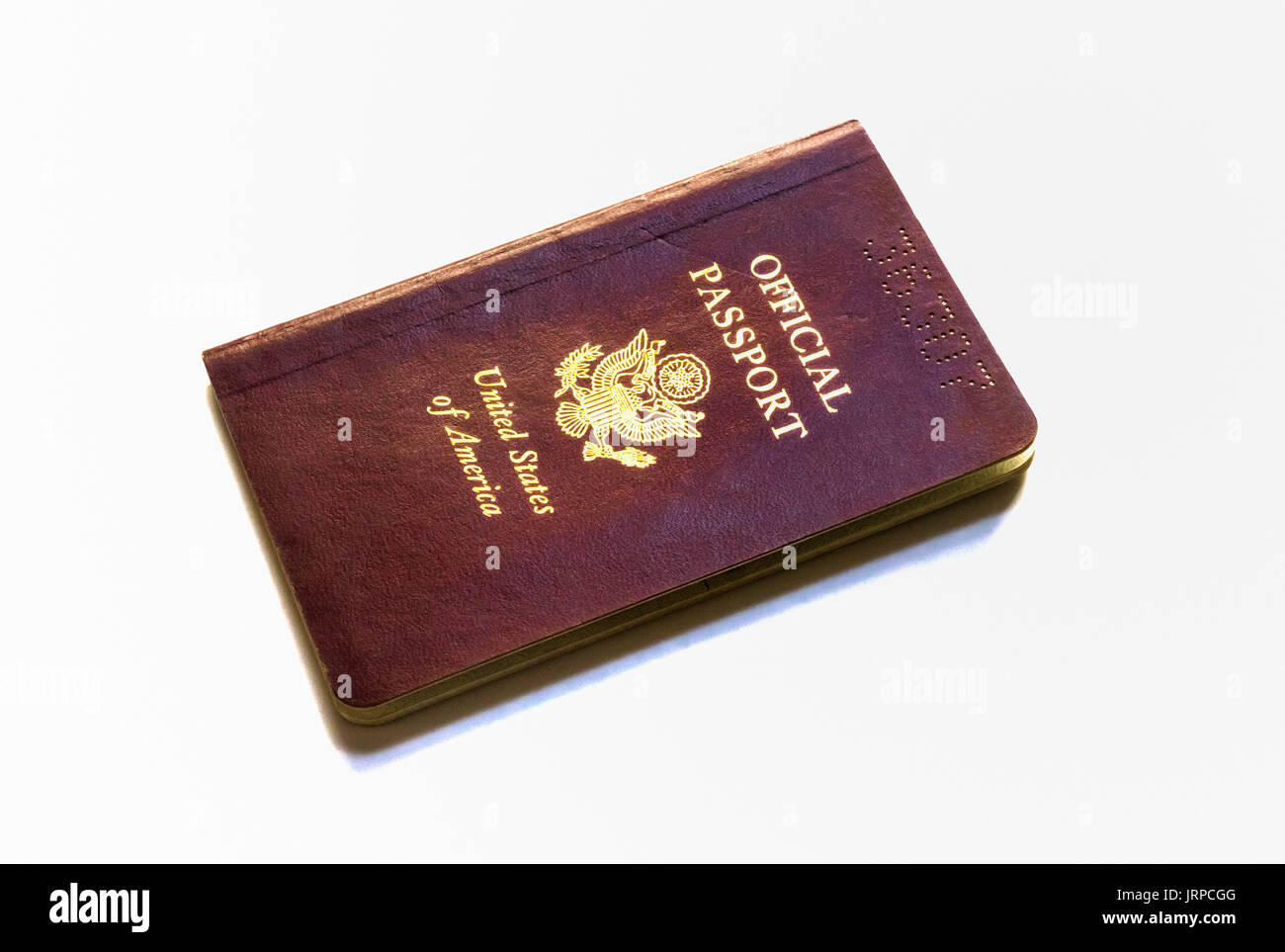 Reddish brown Official US passport shown against a white background - Stock Image
