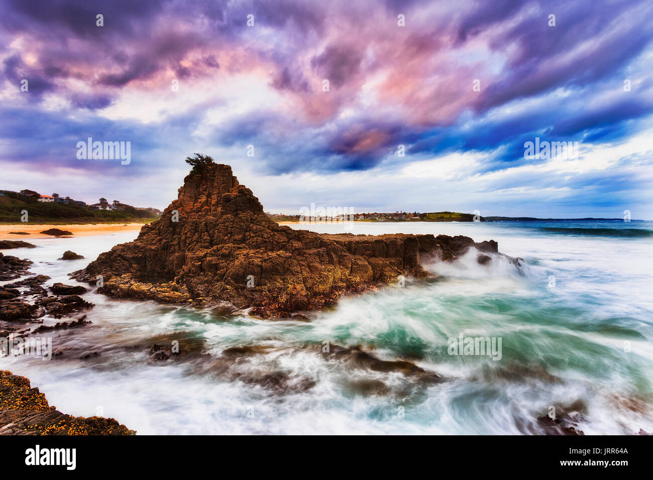 Rugged eroded detached rocky cliff off Kiama Bombo beach on Pacific coast of Australia at sunset with stormy weather. - Stock Image