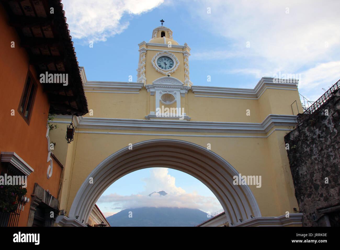 Arco con reloj en la calle principal de La Antigua Guatemala, al fondo se ve el volcán de agua, el arco es icono de la ciudad y un punto de encuentro - Stock Image
