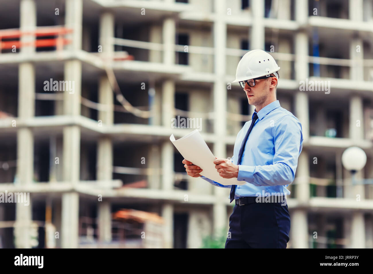 Construction engineer at the construction site looking at the drawing - Stock Image