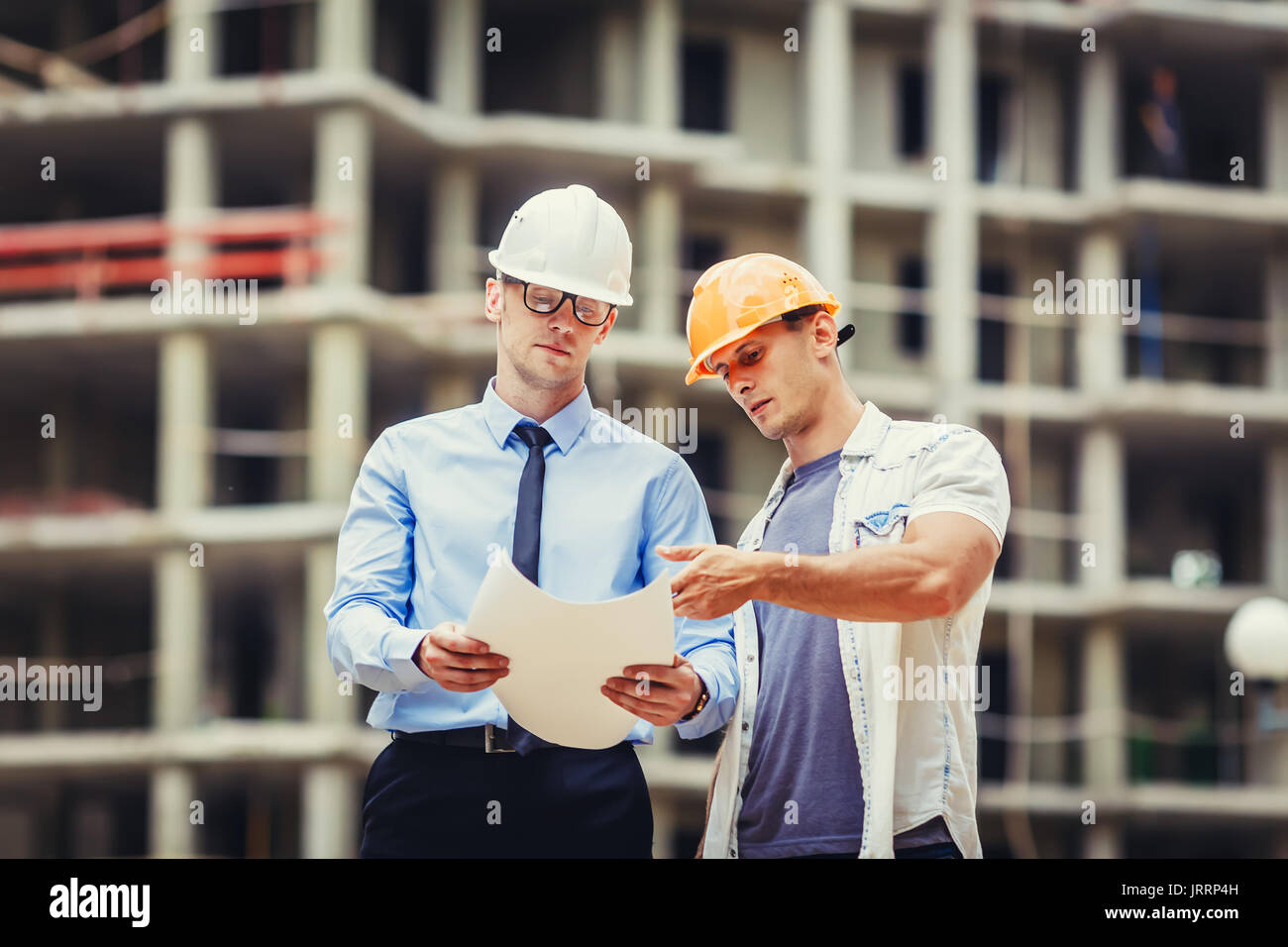 Architect and builder discussing at construction site - Stock Image
