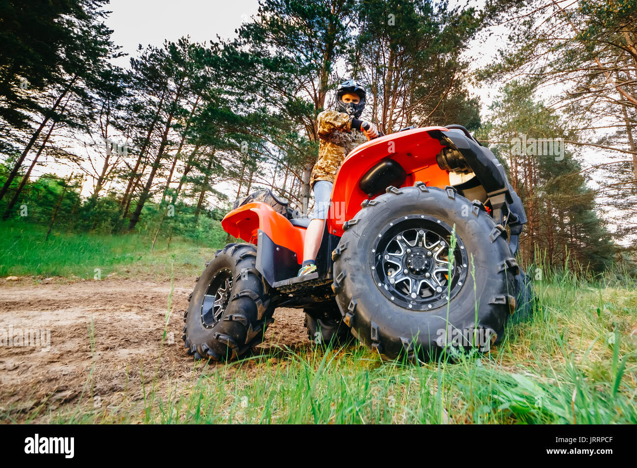 Man on the ATV Quad Bike running in mud track - Stock Image