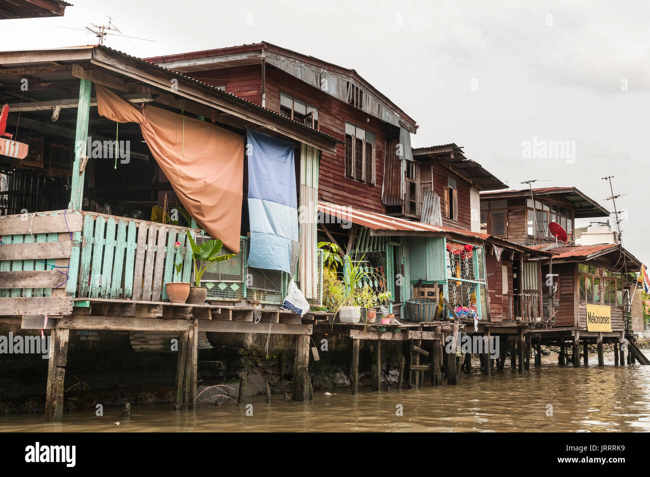 Typical wooden waterside houses on the Khlongs in Thonburi, Bangkok, Thailand - Stock Image