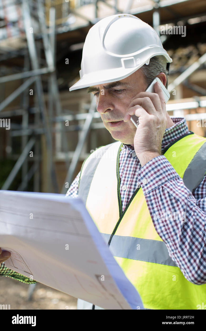 Architect On Building Site Using Mobile Phone - Stock Image